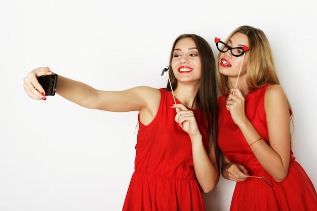 Zwei junge frauen im roten kleid machen selfie
