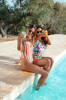 Zwei junge frauen in badeanzügen, die sich entspannen und tropische cocktails im schwimmbad trinken