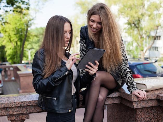Zwei junge frauen in der stadt betrachten den schirm einer tablette und lächeln