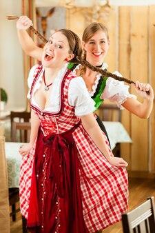 Zwei junge frauen in der traditionellen bayerischen tracht im restaurant oder in der kneipe