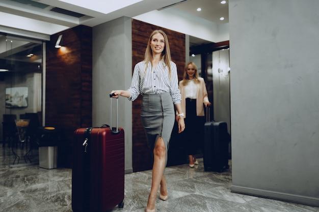 Zwei junge frauen in formeller kleidung betreten die hotellobby