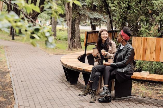Zwei junge frauen in freizeitkleidung essen sandwiches im park