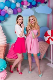 Zwei junge frauen in rosa kleidern trinken saft in einer glasflasche.