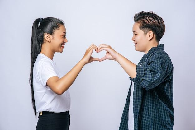 Zwei junge frauen lieben sich handzeichen herzform.