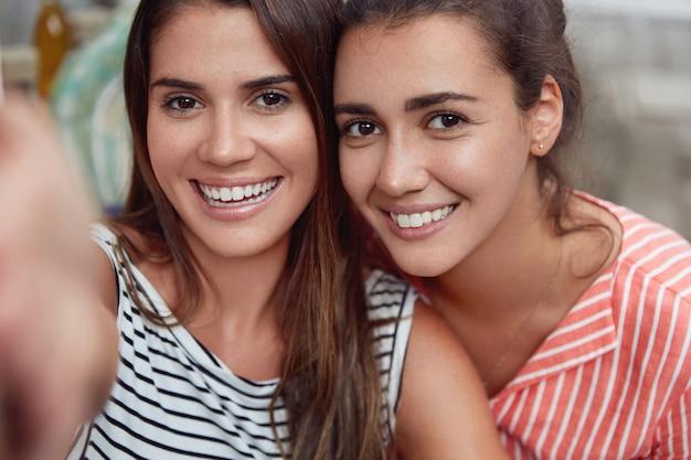 Zwei junge frauen machen selfies mit einem nicht erkennbaren gerät, haben ein breites lächeln, weiße, perfekte zähne, verbringen freizeit miteinander und sind gut gelaunt. hübsche brünette frau macht foto als steht mit freund