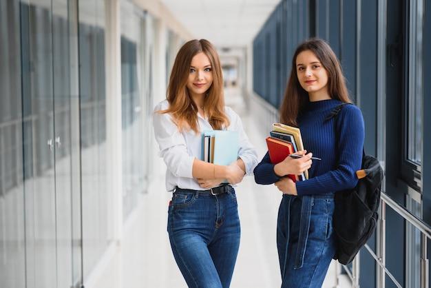 Zwei junge frauen mit buch, das im college-korridor plaudert