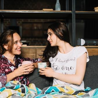 Zwei junge frauen mit dem tasse kaffee einander betrachtend