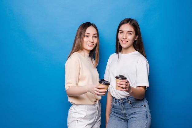 Zwei junge frauen mit kaffeetasse gehen isoliert auf blaue wand
