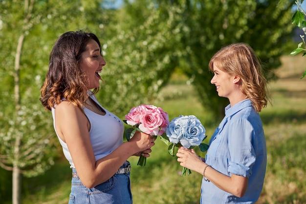 Zwei junge frauen mit rosensträußen auf dem feld. zwei junge frauen mit rosensträußen auf dem feld.