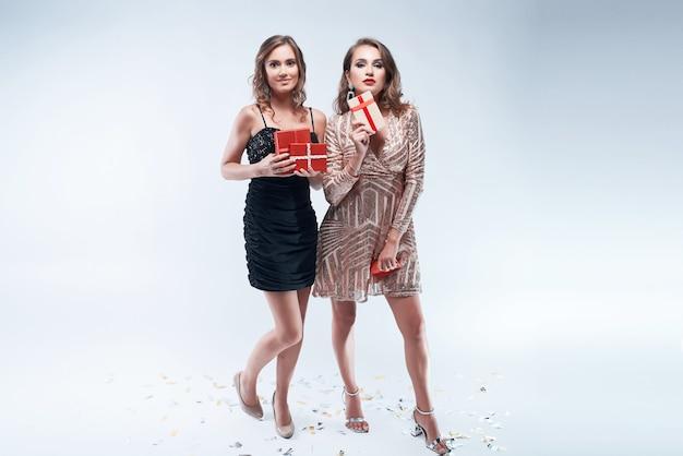 Zwei junge frauen mit roten geschenken in den händen getrennt auf weiß