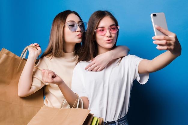 Zwei junge frauen nehmen selfie am telefon mit bunten papiertüten lokalisiert auf blauer wand. konzept für den ladenverkauf.