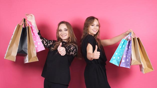 Zwei junge frauen posieren in einem studio mit einer großen anzahl von taschen vor der kamera