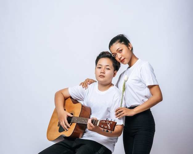 Zwei junge frauen saßen auf einem stuhl und spielten gitarre.