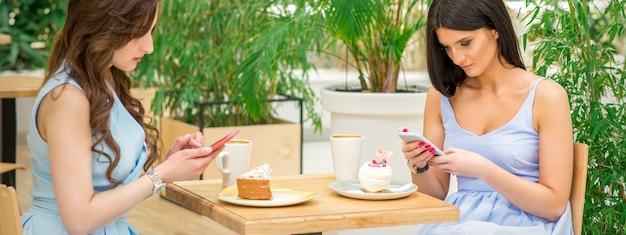 Zwei junge frauen schauen ihre smartphones, während sie in einem café sitzen. technologie menschen sucht