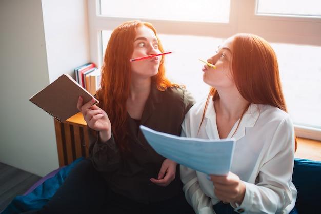 Zwei junge frauen sind müde und haben spaß. sie ahmen mit hilfe von buntstiften einen schnurrbart nach. zwei rothaarige studenten lernen zu hause oder in einem studentenwohnheim. sie bereiten sich auf prüfungen vor.