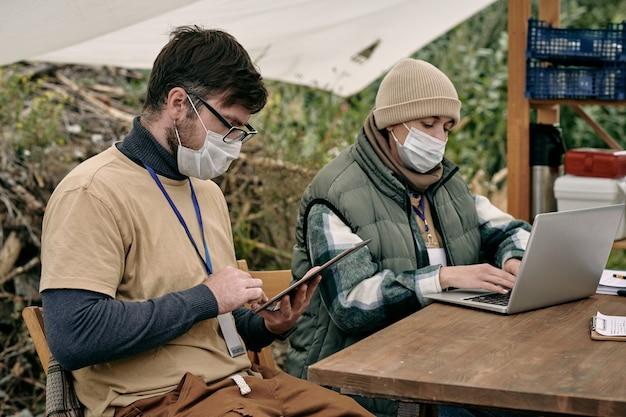 Zwei junge freiwillige mit mobilen geräten