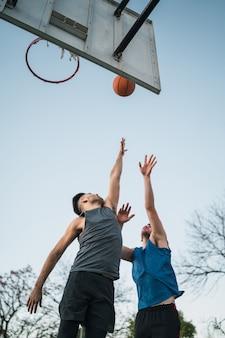 Zwei junge freunde, die basketball spielen.