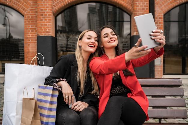 Zwei junge freunde, die ein selfie mit digitalem tablett nehmen.