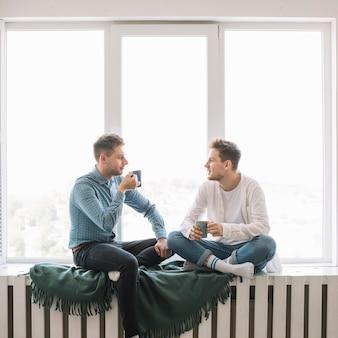 Zwei junge freunde, die mit einander halten die kaffeetasse sitzt nahe fenster sich besprechen