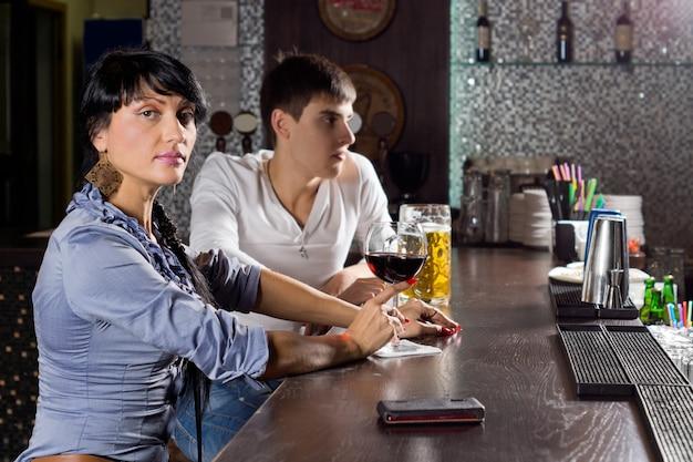 Zwei junge freunde, die zusammen in der kneipe trinken, die an der bartheke sitzt