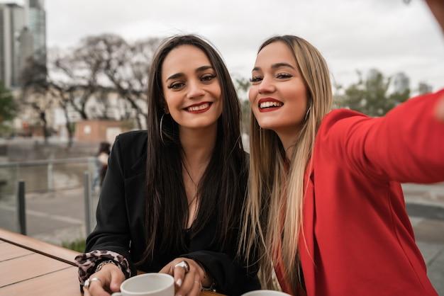 Zwei junge freunde machen zusammen ein selfie im café.