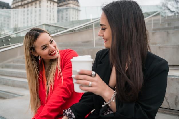 Zwei junge freunde sitzen draußen auf der straße.