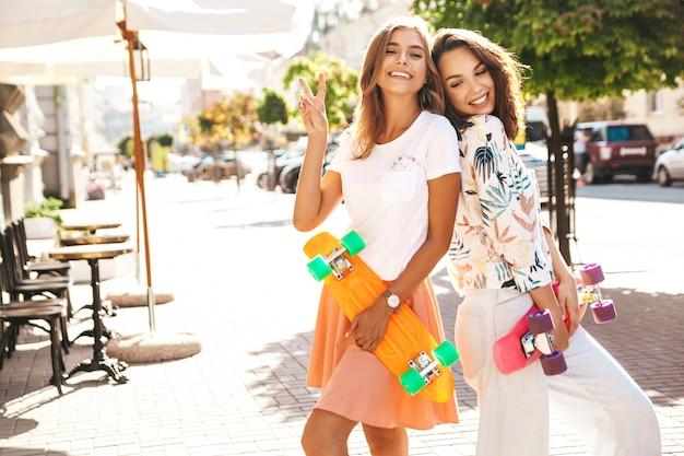 Zwei junge freunde sitzen lächelnd auf penny skateboard auf der straße