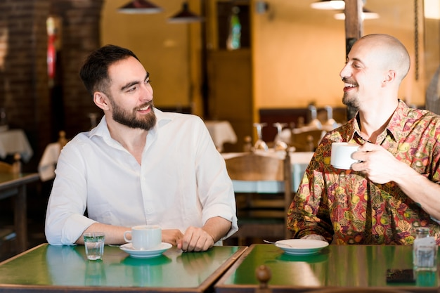 Zwei junge freunde verbringen zeit miteinander, während sie in einem café eine tasse kaffee trinken.