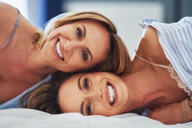 Zwei junge freundinnen auf dem bett. foto in hoher qualität