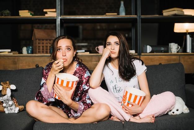Zwei junge freundinnen, die auf dem sofa aufpassendem fernsehen sitzen