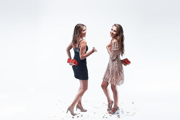 Zwei junge freundinnen, die geschenke hinter dem hinteren gehen halten, um sie zu geben.