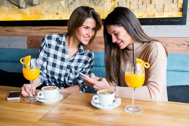 Zwei junge freundinnen, die im café sitzen