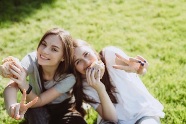 Zwei junge freundinnen, die köstliche burger essen und friedenszeichen mit den fingern im park auf dem gras zeigen. keine gesunde ernährung. weicher selektiver fokus, defokussierung.
