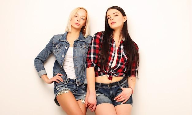 Zwei junge freundinnen, die zusammen stehen und spaß haben. über weißem hintergrund.