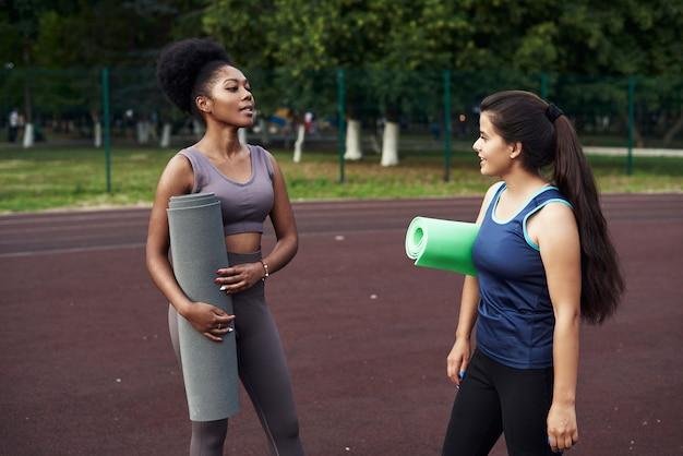 Zwei junge freundinnen sprechen über vergangene workouts im freien