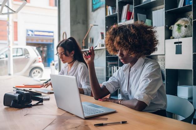 Zwei junge gemischtrassige frauen, die mit digitalem gerät in modernen coworking-raum schreiben und arbeiten