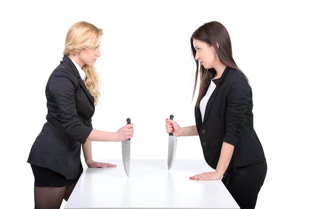 Zwei junge geschäftsfrau, die hände rüttelt und messer hält.