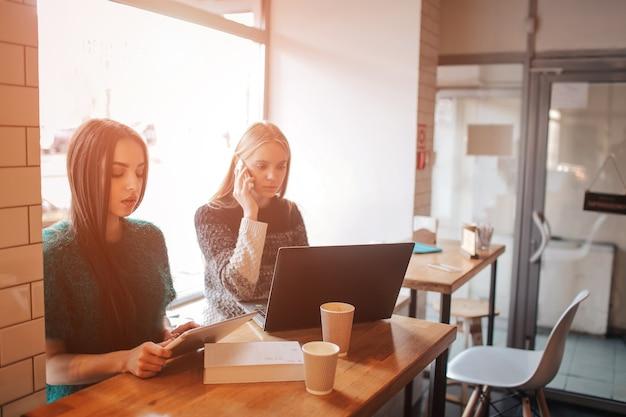 Zwei junge geschäftsfrauen, die am tisch im café sitzen. mädchen, das teamwork-geschäftstreffen des smartphone-bloggens verwendet