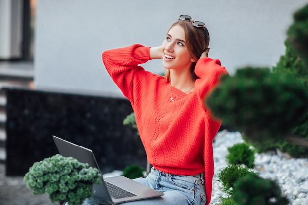 Zwei junge geschäftsfrauen, die zusammen in einer café-terrasse mittagspause machen, mit laptop und notebook.