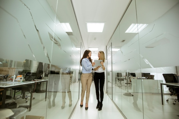 Zwei junge geschäftsfrauen mit digitaler tablette im büro