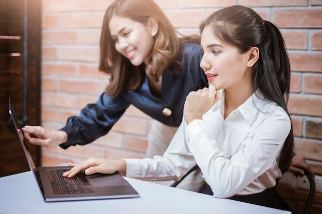 Zwei junge geschäftsfrauen sind analytische informationen auf laptopbildschirm, geschäftstreffen
