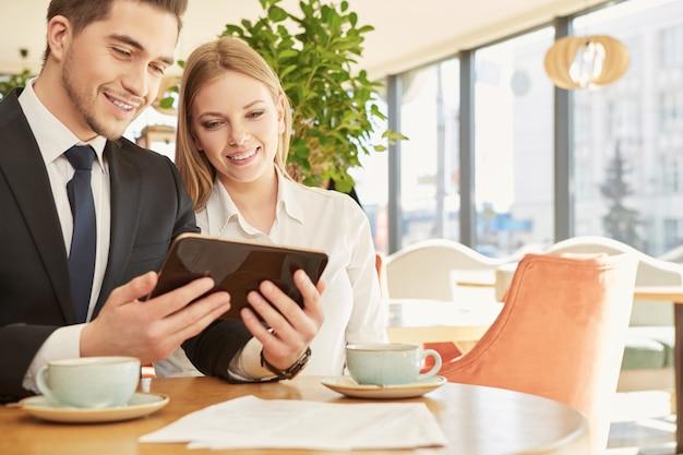 Zwei junge geschäftskollegen, die digitale tablette an der kaffeestube verwenden