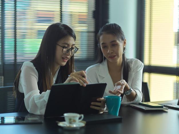 Zwei junge geschäftsleute beraten sich bei ihrem projekt im besprechungsraum
