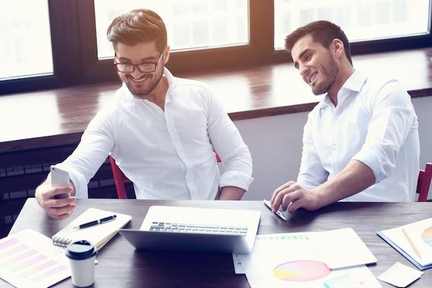 Zwei junge geschäftsleute, die am modernen büro arbeiten. filmeffekt, linseneffekt