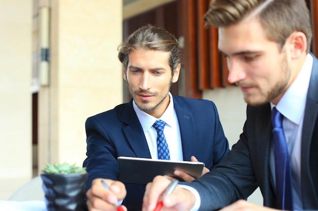 Zwei junge geschäftsleute, die beim treffen touchpad verwenden.