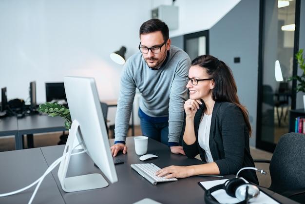 Zwei junge geschäftsleute, die computerüberwachungsgerät betrachten. gemeinsam an einem projekt arbeiten.