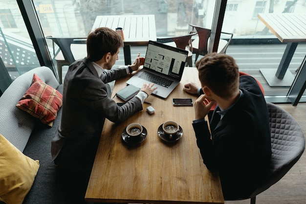 Zwei junge geschäftsleute, die ein erfolgreiches treffen im restaurant haben.