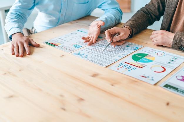Zwei junge geschäftsleute sitzen am holztisch, während sie dokumente mit finanzinformationen beim arbeitstreffen besprechen