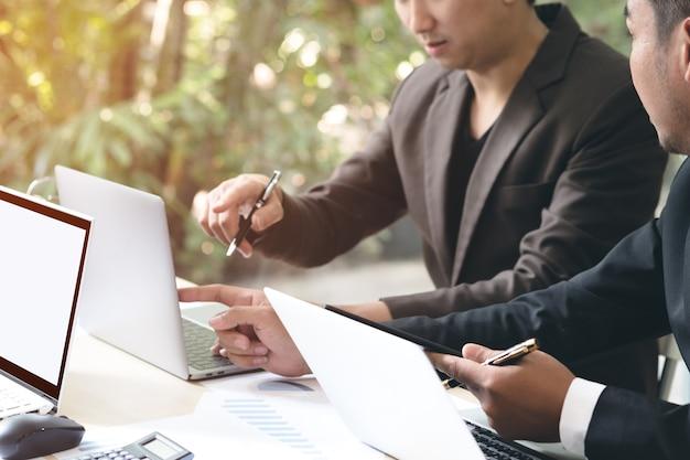 Zwei junge geschäftsmänner, die laptop und notenauflage bei der sitzung im büro verwenden.