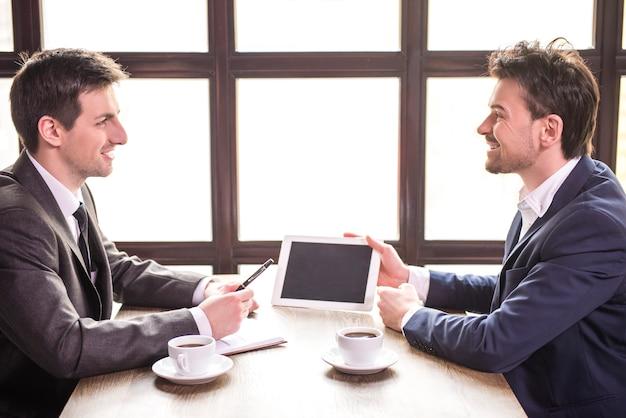 Zwei junge geschäftsmänner, die während eines business-lunchs arbeiten.